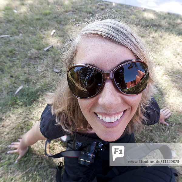 Caucasian woman in sunglasses holding camera