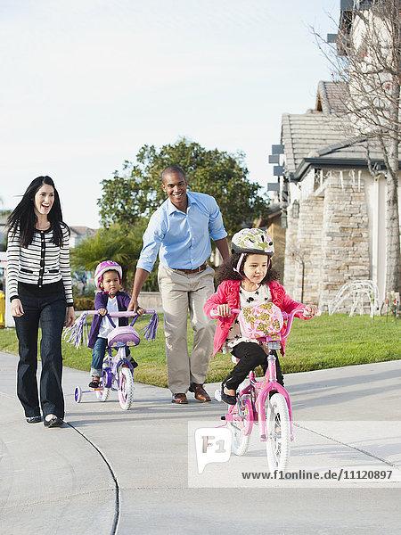 Parents watching children ride bicycles