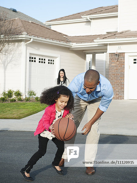 Father and daughter playing basketball in road