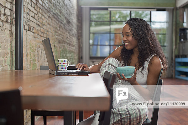 Mixed race woman having breakfast and using laptop