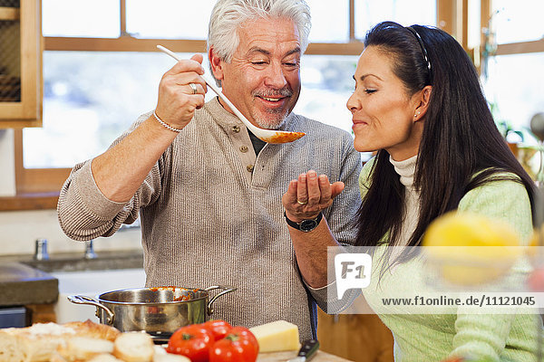 Hispanic couple cooking together in kitchen