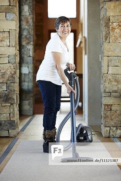 Older Hispanic woman vacuuming carpet