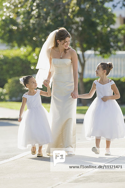 Multi-ethnic bride holding hands with flower girls