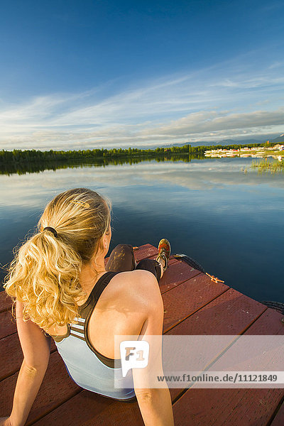 Caucasian woman relaxing on dock on still lake  Anchorage  Alaska  United States