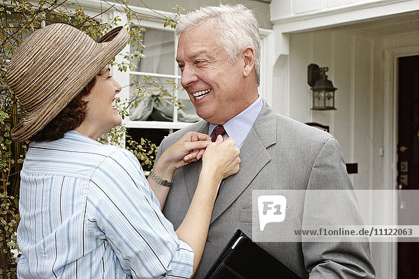 Woman adjusting husband's tie on front path