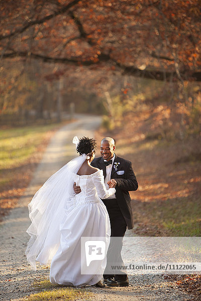 Bride and groom standing on path