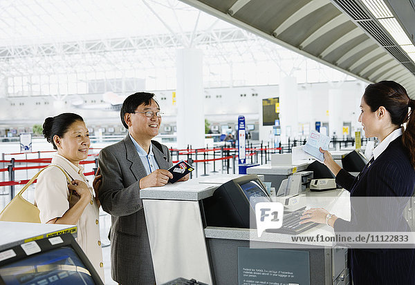 Asian couple checking in at airport