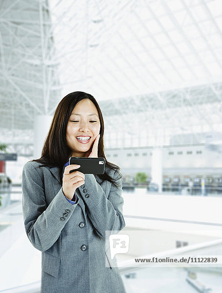 Asian woman checking cell phone in airport