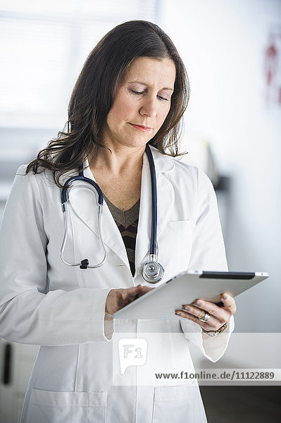 Caucasian doctor using tablet computer in office
