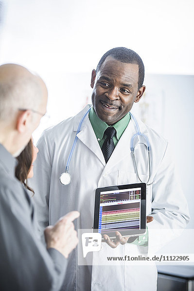 Doctor showing tablet computer to patients