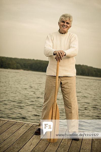 Older Caucasian man holding oar on wooden dock