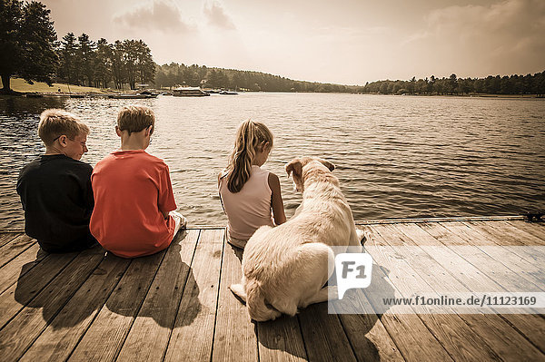 Caucasian children sitting on wooden dock with dog