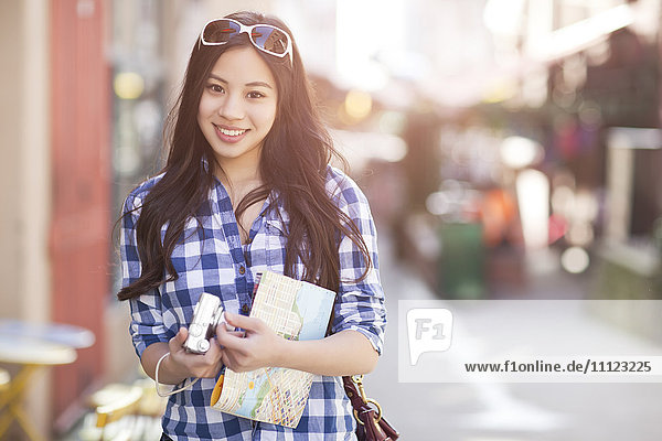 Chinese woman holding map and digital camera