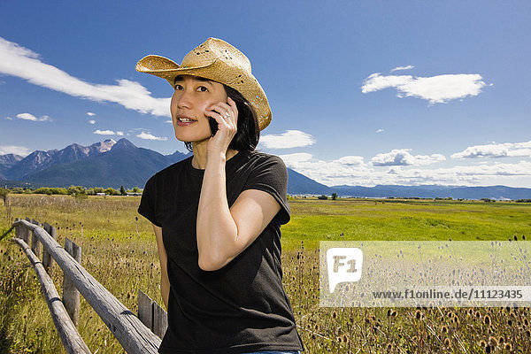 Japanese woman talking on cell phone in country field