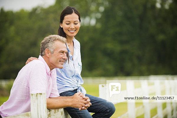 Couple relaxing together on fence