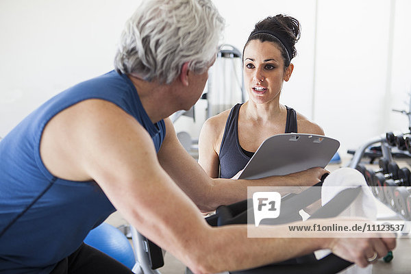 Older Hispanic man working with trainer in gym