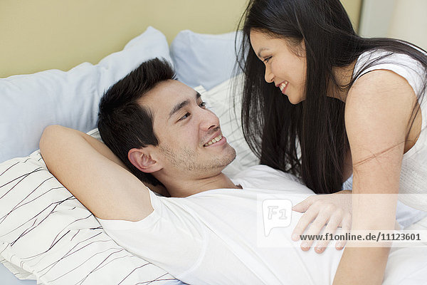 Woman smiling at husband in bed