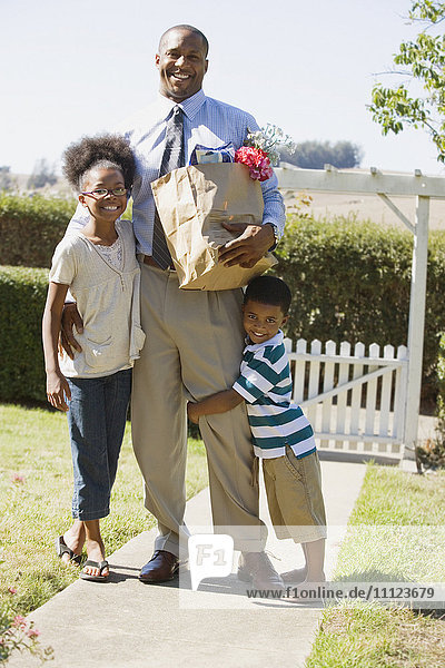 African father with groceries hugging children
