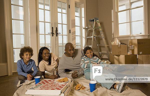 Family eating on floor in new home