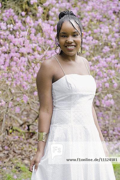 Mixed race woman wearing dress in garden