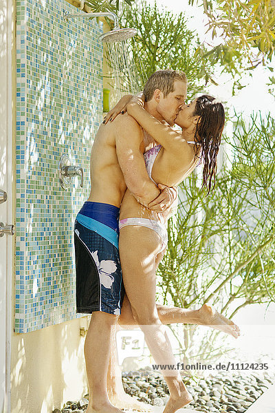 Couple kissing underneath outdoor shower
