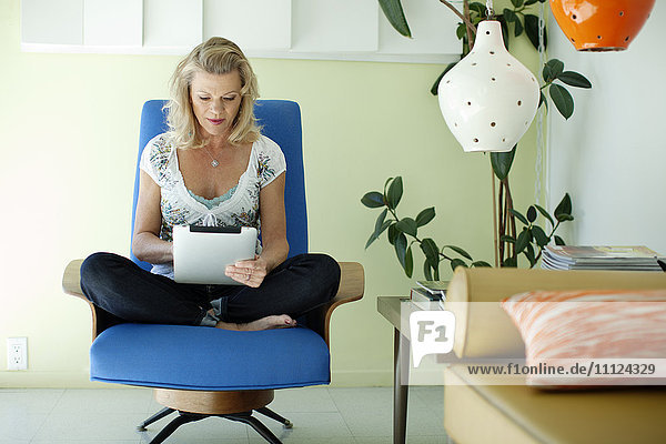 Caucasian woman using digital tablet in living room
