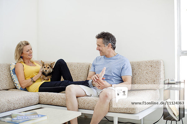 Couple relaxing with dog on sofa