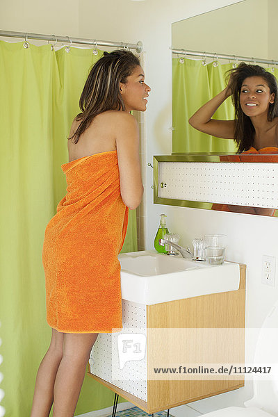Mixed race woman wrapped in towel looking in mirror
