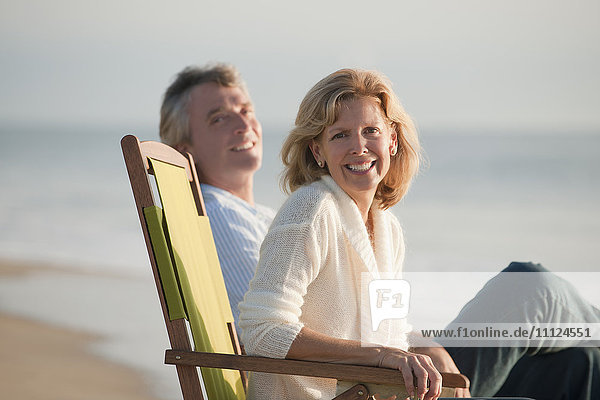 Caucasian couple sitting on folding chairs on beach