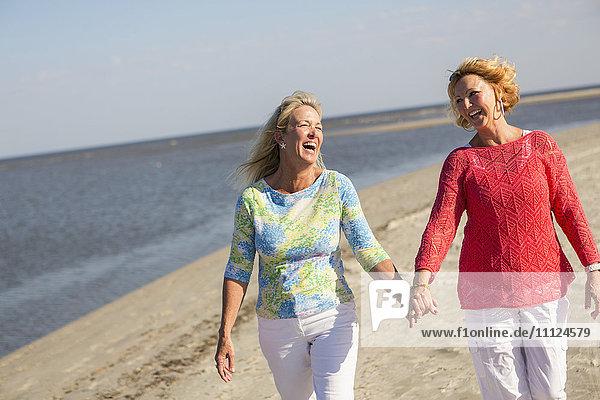 Caucasian women walking on beach