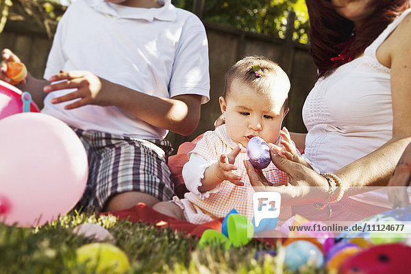 Hispanic baby playing with Easter eggs