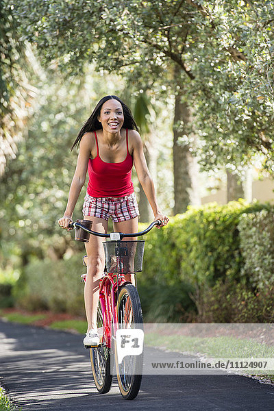 Hispanic woman riding bicycle outdoors