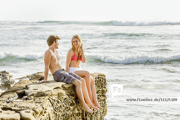 Couple relaxing on rocky beach