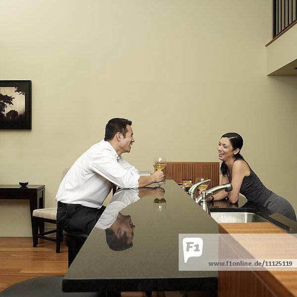 Asian couple talking in kitchen