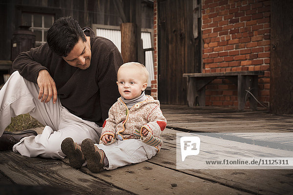 Caucasian father sitting on floor with son Caucasian father sitting on floor with son