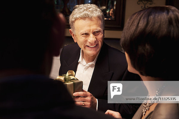 Caucasian man giving woman gift in restaurant