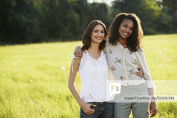 Portrait of two women hugging in meadow