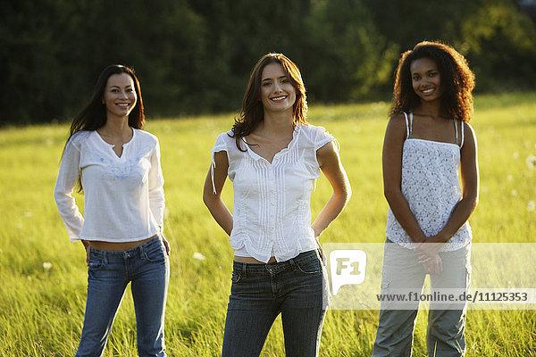 Three women standing in meadow