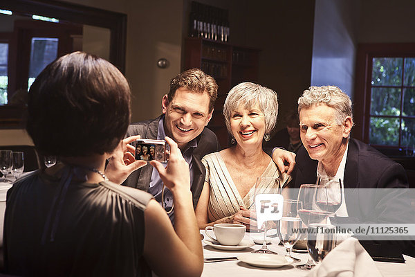 Woman photographing friends in restaurant
