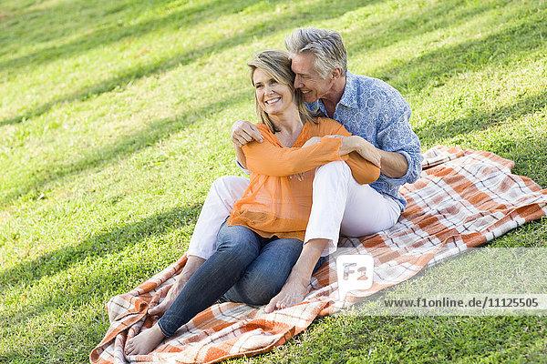 Caucasian couple relaxing in grass