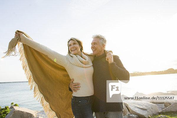 Caucasian couple walking by lake