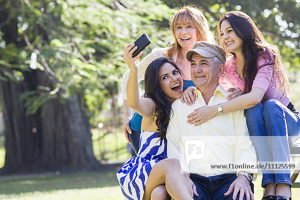 Hispanic family taking pictures together outdoors