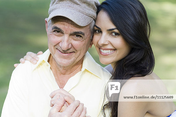 Hispanic father and daughter smiling outdoors
