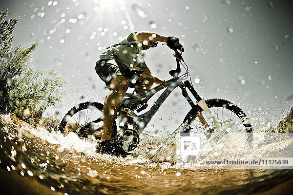 Man riding mountain bike through water