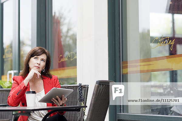 Caucasian businesswoman using tablet at cafe