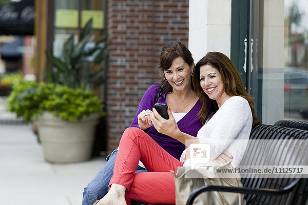 Caucasian women using cell phone on city bench