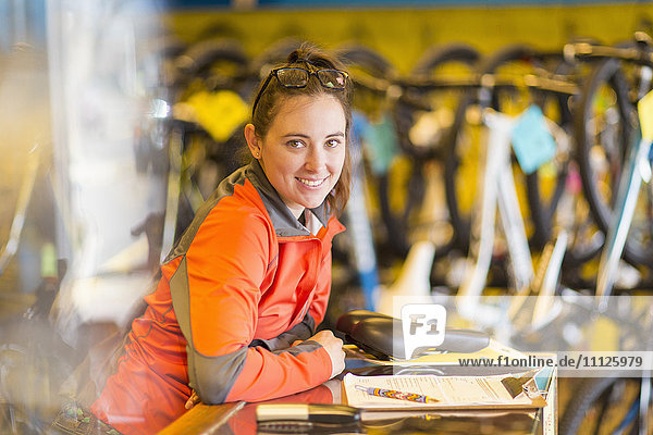 Caucasian woman smiling in bicycle shop