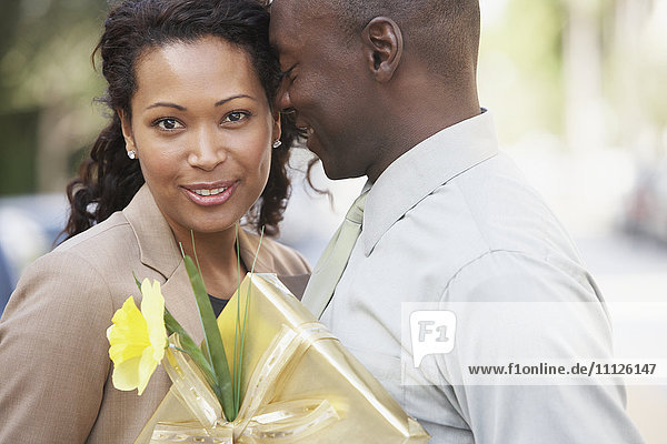African couple hugging and holding gift