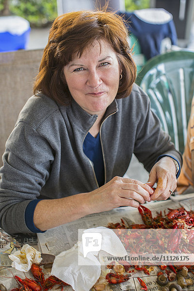Caucasian woman eating crawfish at boil