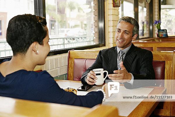 Hispanic business people talking in restaurant